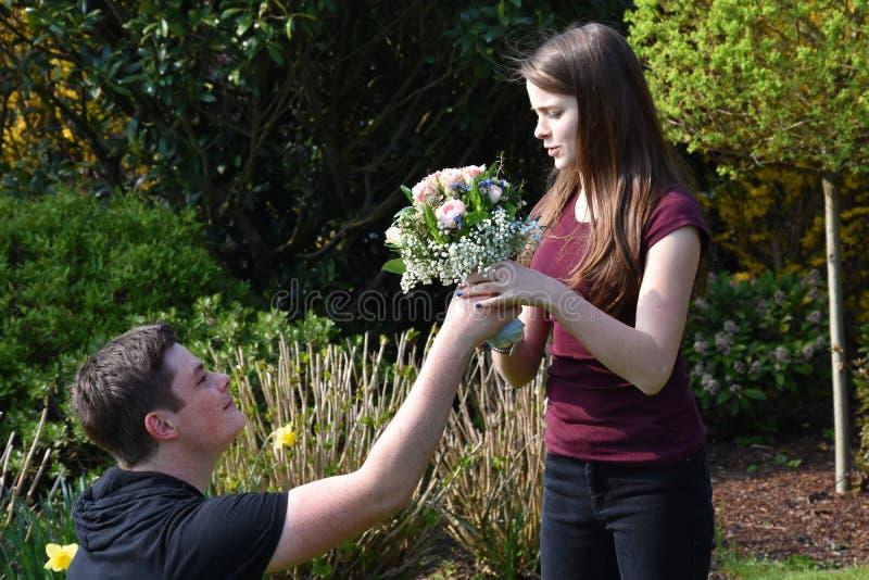 O menino dá flores a sua amiga fotografia de stock