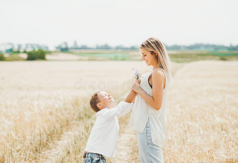 O menino dá a sua mãe um ramalhete dos wildflowers no campo de trigo ensolarado foto de stock