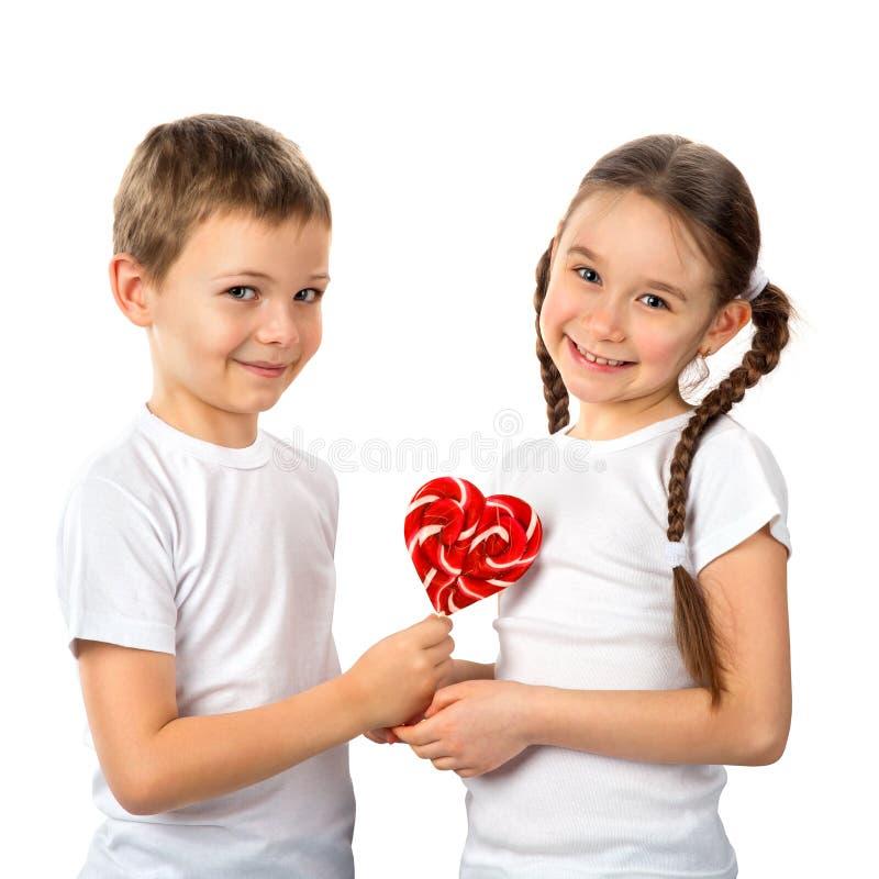 O menino dá a uma menina o coração do pirulito dos doces isolado no branco Dia do `s do Valentim Amor das crianças imagem de stock