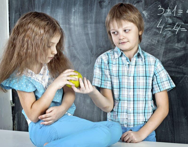 O menino dá a uma menina uma maçã na escola fotografia de stock