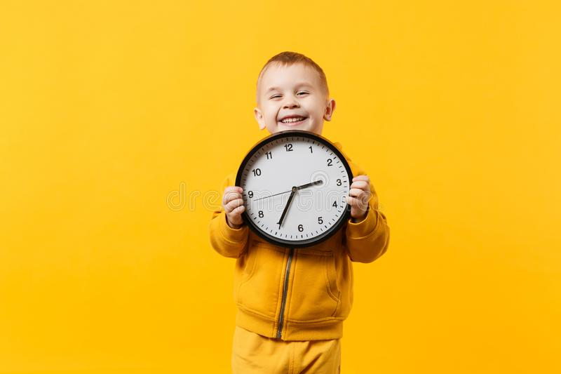 O menino da criança 3-4 anos de roupa amarela vestindo velha mantém o pulso de disparo isolado no fundo alaranjado da parede, est foto de stock royalty free