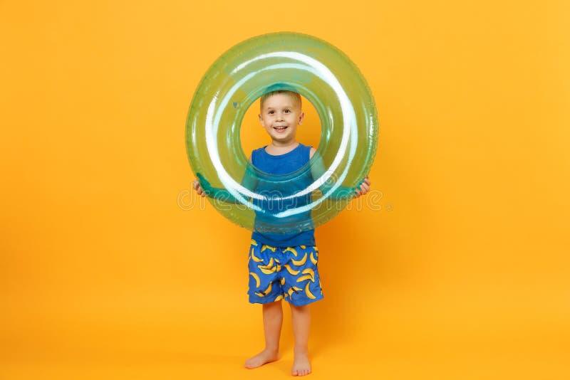 O menino da criança 3-4 anos velho na roupa azul do verão da praia mantém o anel inflável isolado no fundo alaranjado amarelo bri imagem de stock royalty free