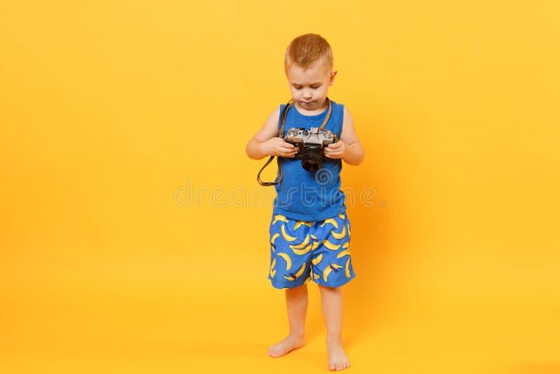O menino da criança 3-4 anos velho na roupa azul do verão da praia mantém a câmera retro isolada no fundo alaranjado amarelo bril imagem de stock