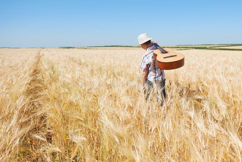 O menino da criança com guitarra está no campo de trigo amarelo, sol brilhante, paisagem do verão foto de stock