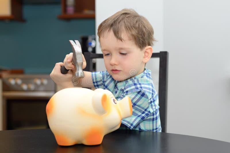 O menino da criança de 4 anos está preparando-se para quebrar o mealheiro imagens de stock royalty free