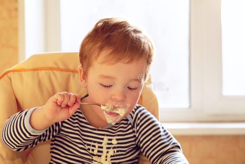 O menino da criança de dois anos come o papa de aveia na manhã. imagem de stock