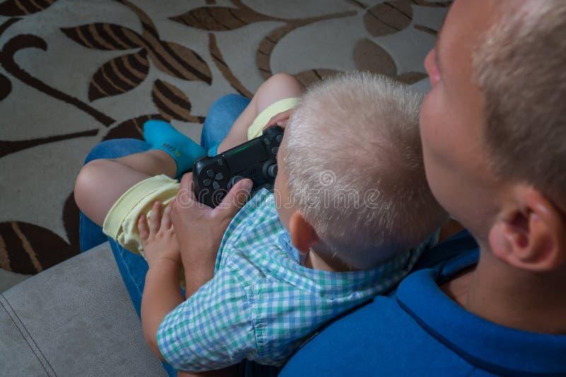 O menino da criança e seu pai jogam com um playstation junto imagem de stock royalty free
