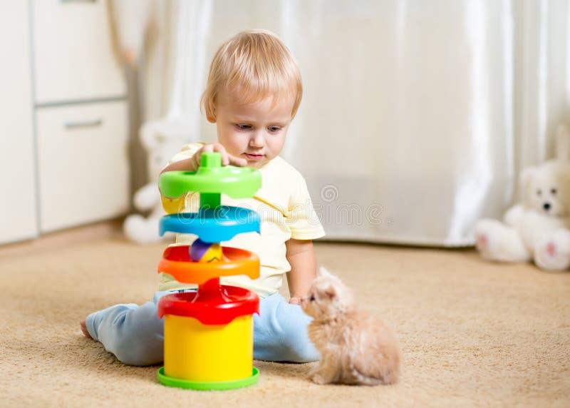 O menino da criança joga com um gatinho, um interior imagem de stock