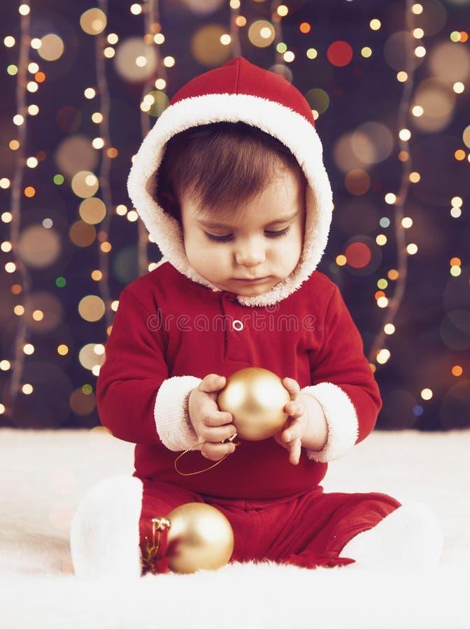 O menino da criança pequena vestido como Santa que joga com decoração do Natal, fundo escuro com iluminação e boke ilumina-se, HO fotografia de stock