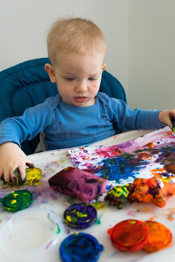 O menino da criança tira com pinturas do dedo no papel na tabela das crianças fotografia de stock