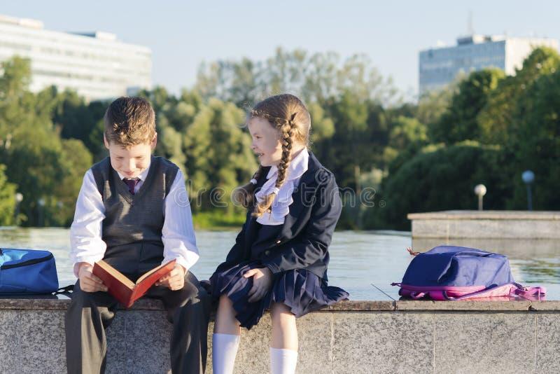 O menino da escola lê o livro que a menina pede seu nome, a atitude dos estudantes fotografia de stock