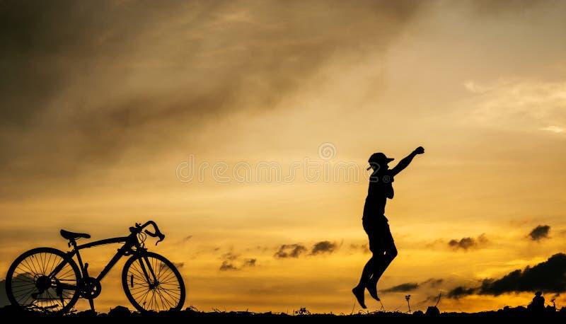 O menino da silhueta salta durante o tempo do por do sol foto de stock