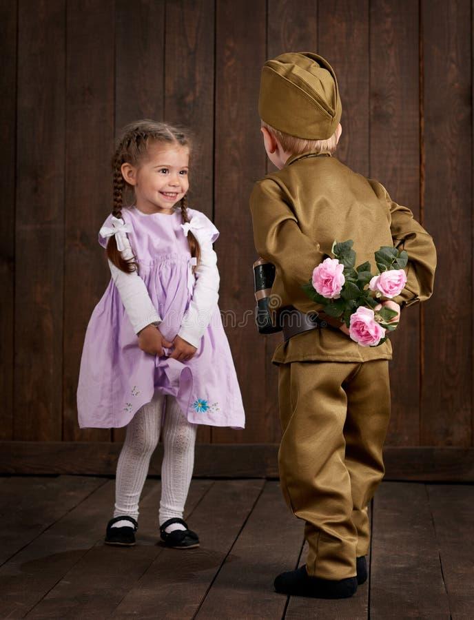 O menino das crianças é vestido como o soldado em uniformes militares retros e em menina no vestido cor-de-rosa fotos de stock royalty free