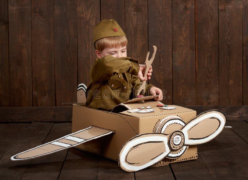 O menino das crianças é vestido como o soldado em uniformes militares retros repara um avião feito da caixa de cartão, fundo de m imagem de stock