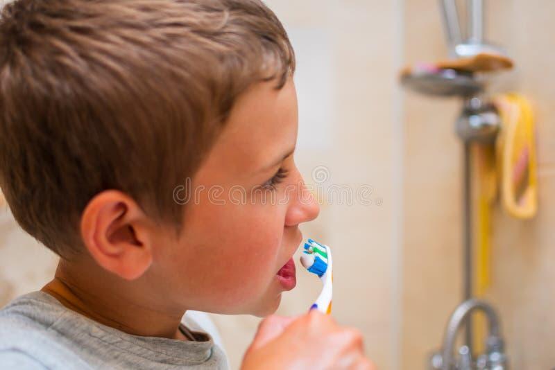 O menino de 10 anos escova seus dentes no banheiro fotos de stock royalty free