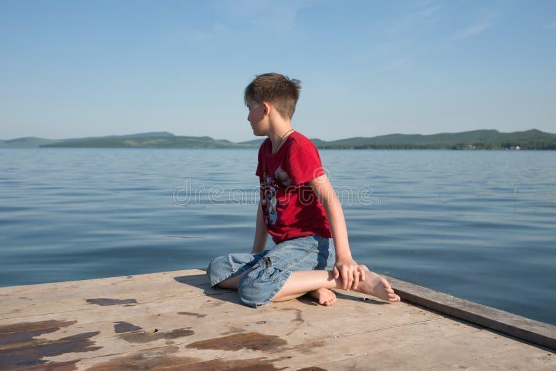 O menino de 11 anos velho senta-se em um cais de madeira e em olhares na água do lago em um dia ensolarado foto de stock