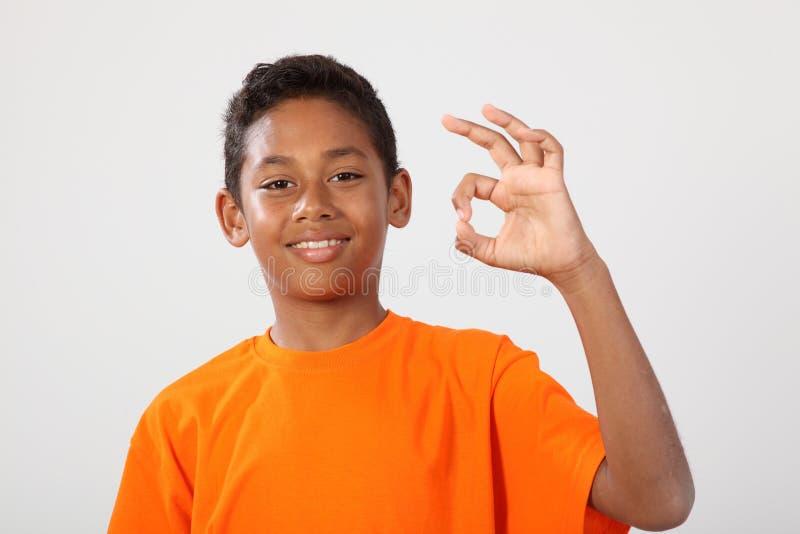 O menino de escola étnico feliz 11 faz o sinal aprovado da mão imagem de stock royalty free