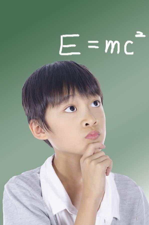 O menino de escola está pensando fotografia de stock royalty free