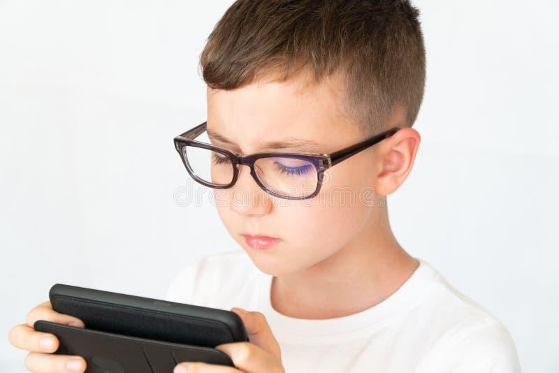 O menino de escola olha o vídeo considerável do smartphone, nos vidros, infelizes fotografia de stock