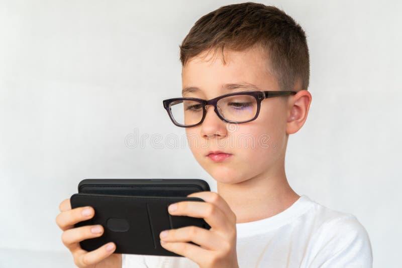 O menino de escola olha o vídeo considerável do smartphone, nos vidros imagem de stock royalty free