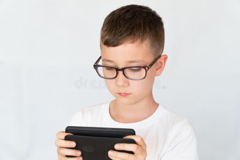 O menino de escola olha o vídeo considerável do smartphone, nos vidros imagens de stock