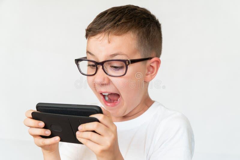O menino de escola olha o vídeo e gritos consideráveis do smartphone no susto imagens de stock royalty free