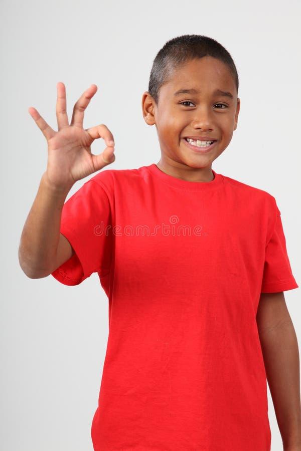 O menino de escola preto novo 9 dá o sinal aprovado feliz imagem de stock royalty free