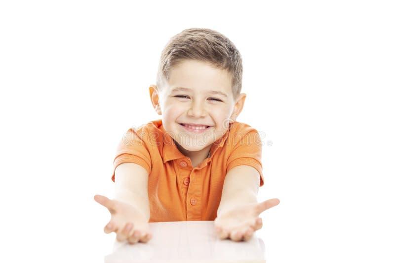 O menino de riso bonito da idade escolar em um t-shirt alaranjado senta-se na tabela, braços estendidos Isolado em um fundo branc fotos de stock