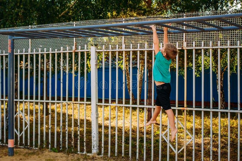 O menino de sete anos é contratado em barras horizontais da rua imagem de stock royalty free