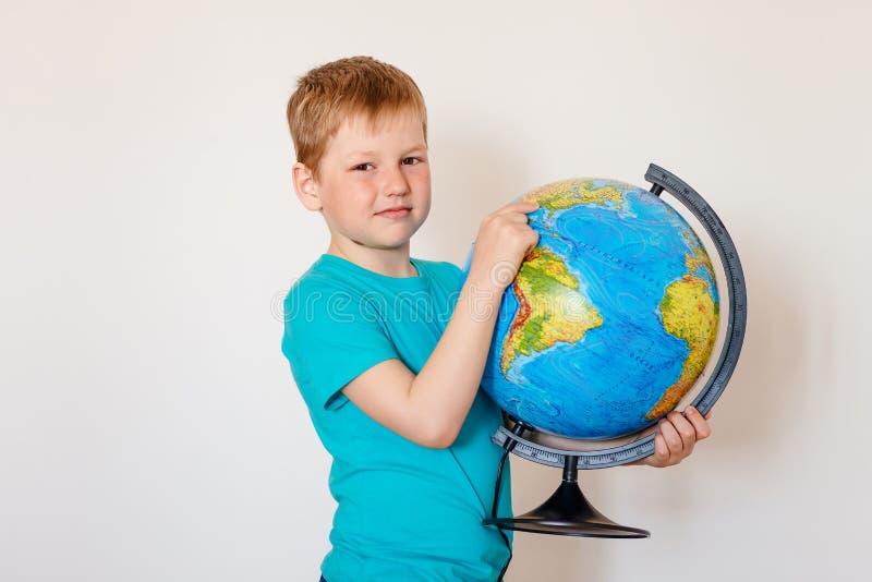 O menino de sete anos guarda o globo fotografia de stock
