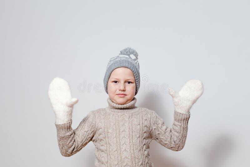 O menino de sete anos nos mitenes e na camiseta feitos malha brancos espalha suas mãos aos lados fotografia de stock