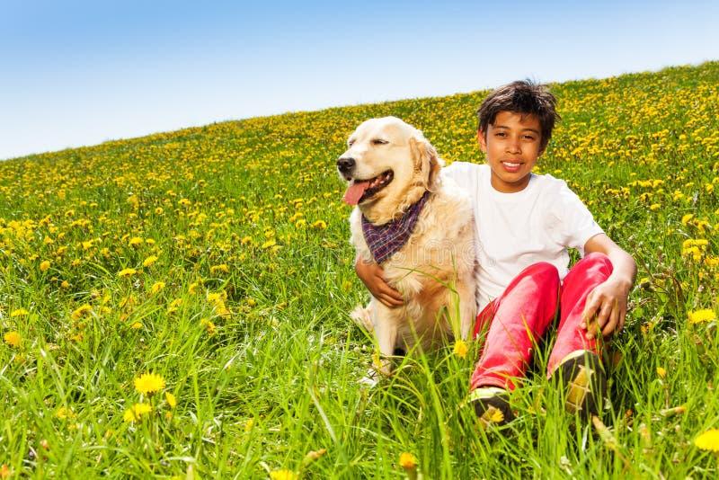 O menino de sorriso abraça o cão bonito que senta-se na grama verde imagem de stock