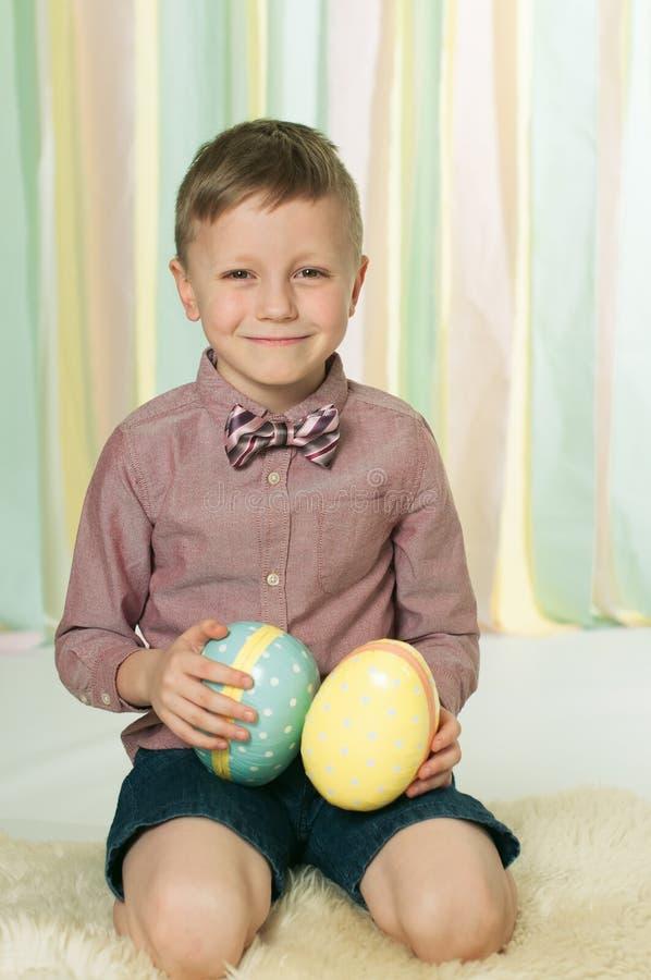 O menino de sorriso com um laço que senta-se no assoalho com os ovos da páscoa em suas mãos imagens de stock royalty free