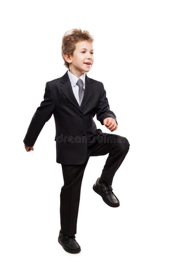 O menino de sorriso da criança do homem de negócios que anda para a realização seguinte pisa imagens de stock royalty free