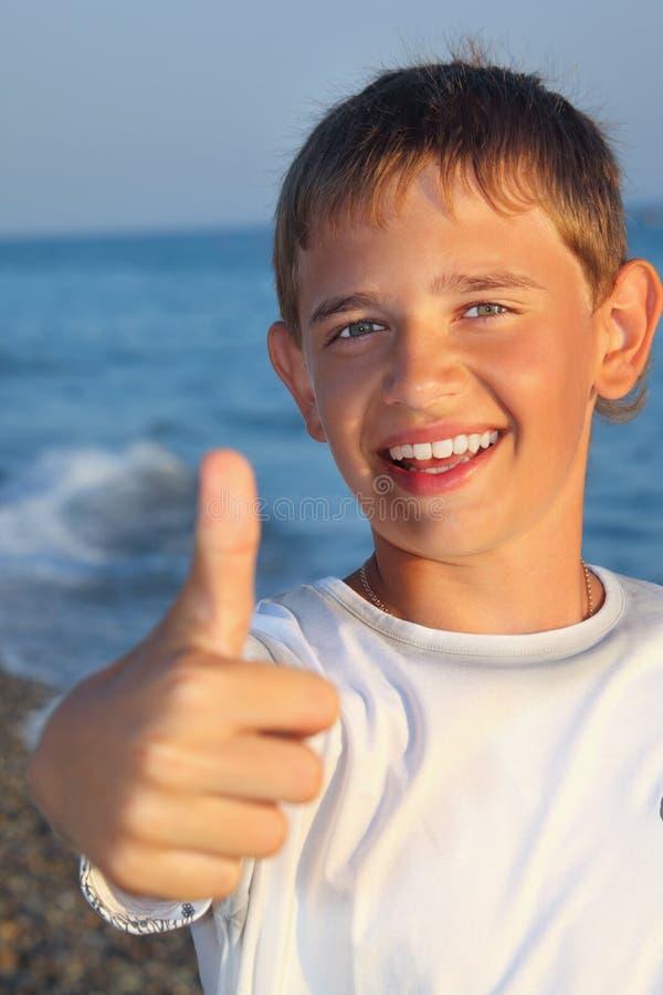O menino de sorriso do adolescente de encontro ao mar mostra a aprovação do gesto imagem de stock