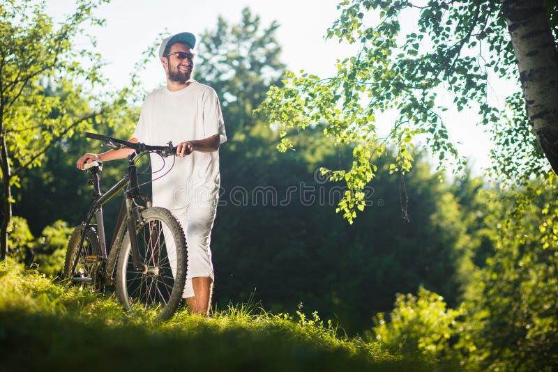 O menino de sorriso do esporte está em uma grama com a bicicleta exterior foto de stock