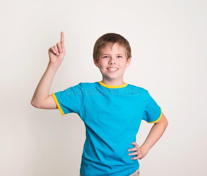 O menino de sorriso do preteen com boa ideia mantém o dedo isolado acima em w imagem de stock