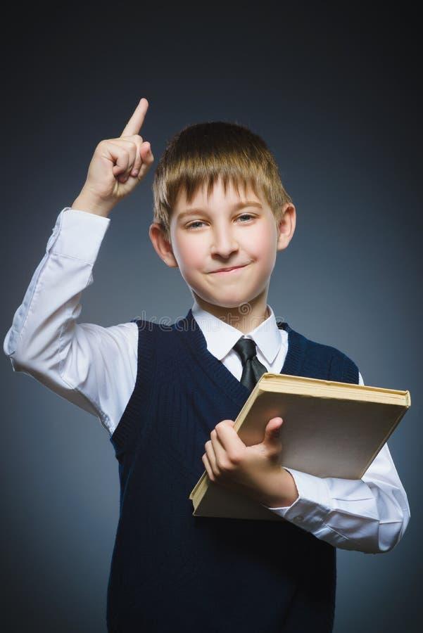 O menino de sorriso do preteen tem a ideia com o livro que guarda o dedo acima no fundo cinzento imagem de stock
