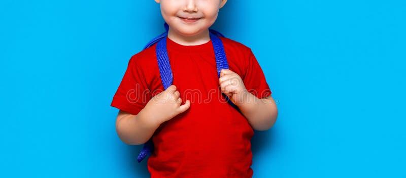 O menino de sorriso feliz no t-shirt vermelho com vidros em sua cabeça está indo educar pela primeira vez Crian?a com saco de esc imagem de stock royalty free