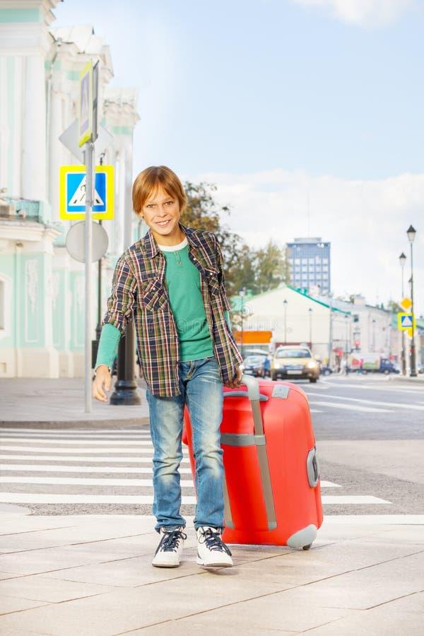 O menino de sorriso guarda a bagagem vermelha e anda na rua fotografia de stock