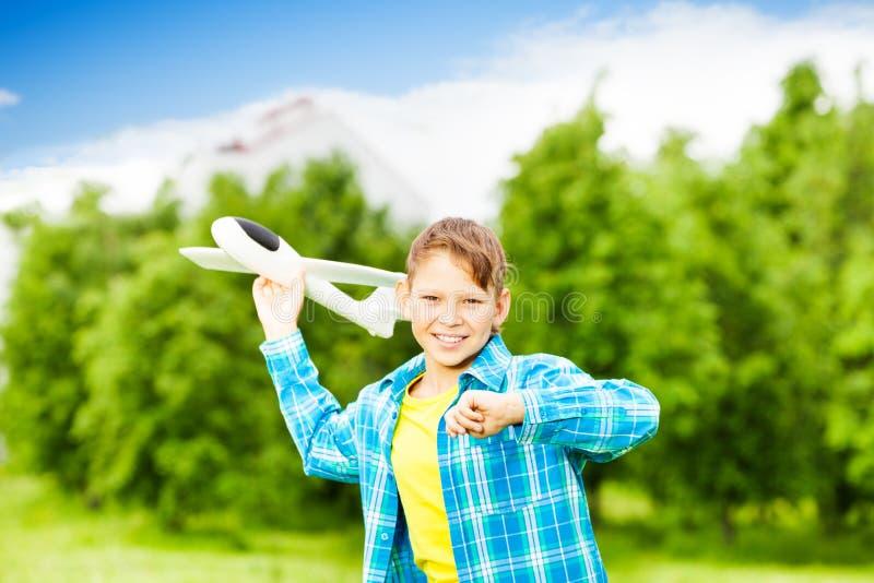 O menino de sorriso guarda o brinquedo branco do avião no prado fotografia de stock royalty free