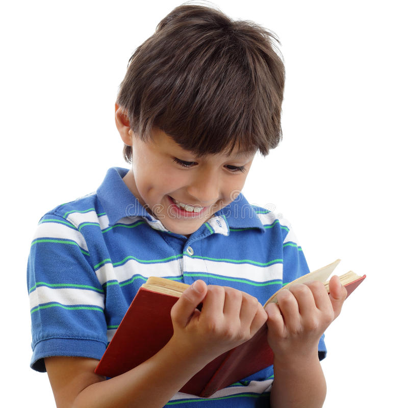 O menino de sorriso lê o livro fotografia de stock royalty free