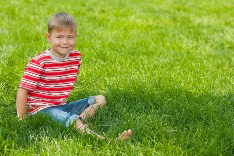 O menino de sorriso senta-se na grama verde imagem de stock
