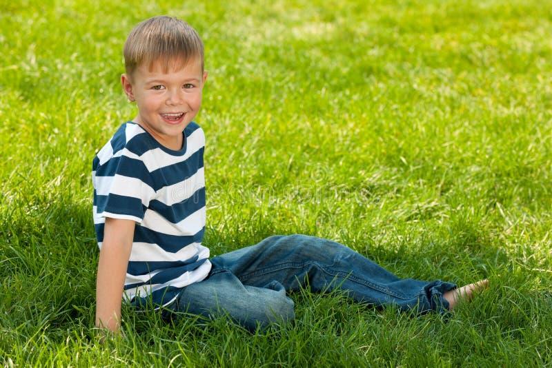 O menino de sorriso senta-se no parque do verão imagens de stock royalty free