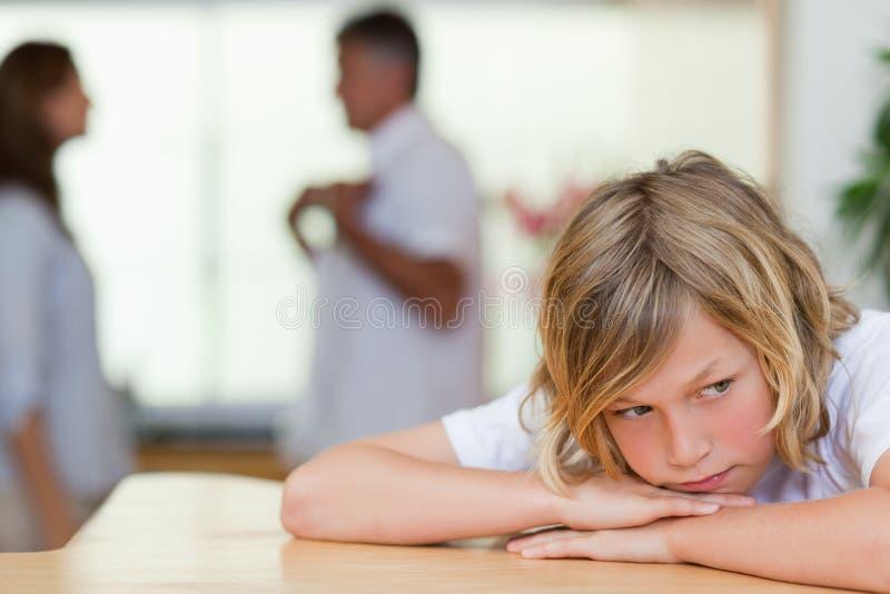 O menino de vista triste com luta parents atrás dele foto de stock royalty free