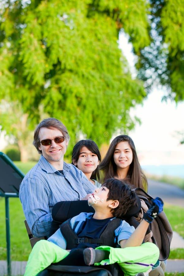 O menino deficiente na cadeira de rodas com família fora no dia ensolarado senta-se imagem de stock