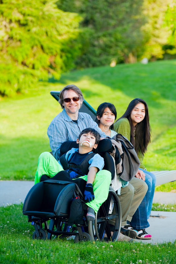 O menino deficiente na cadeira de rodas com família fora no dia ensolarado senta-se fotos de stock royalty free