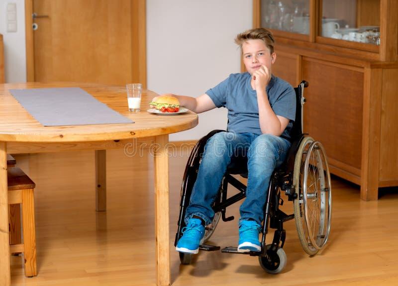 O menino deficiente na cadeira de rodas está comendo fotos de stock