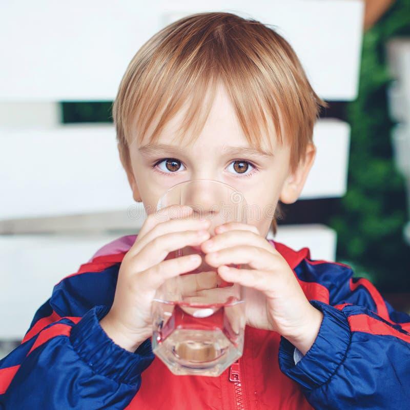 O menino desportivo pequeno bonito bebe a água Criança fora A criança guarda um vidro da água Criança com um vidro da água fresca fotos de stock royalty free