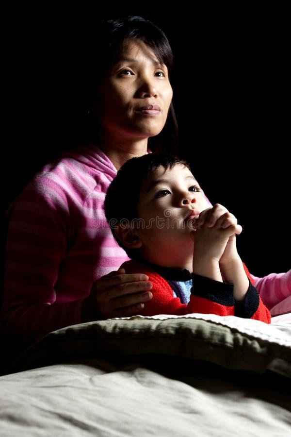 O menino diz orações com matriz. foto de stock